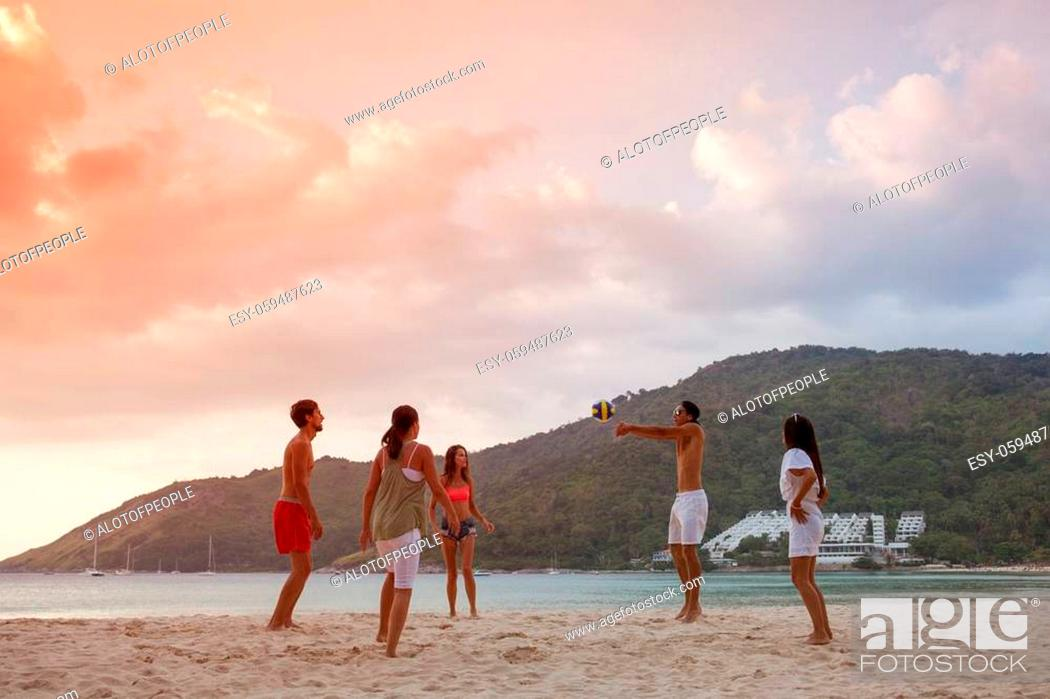 Stock Photo: Group of young people playing volleyball on beach at sunset.