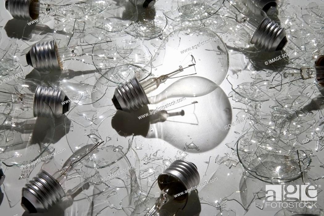 Stock Photo: Lightbulb surrounded by broken bulbs.
