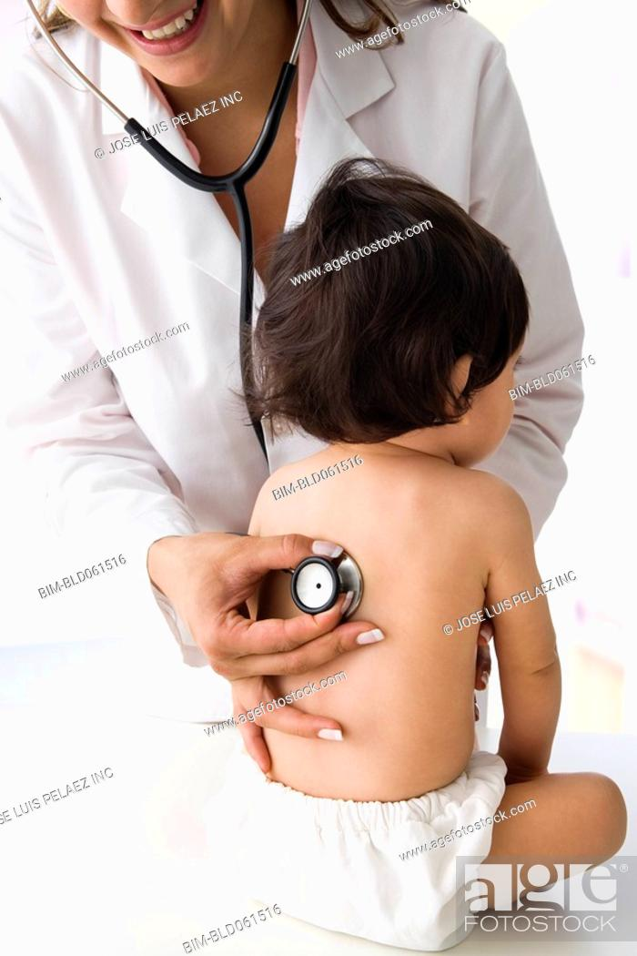 Stock Photo: Hispanic baby being examined by doctor.
