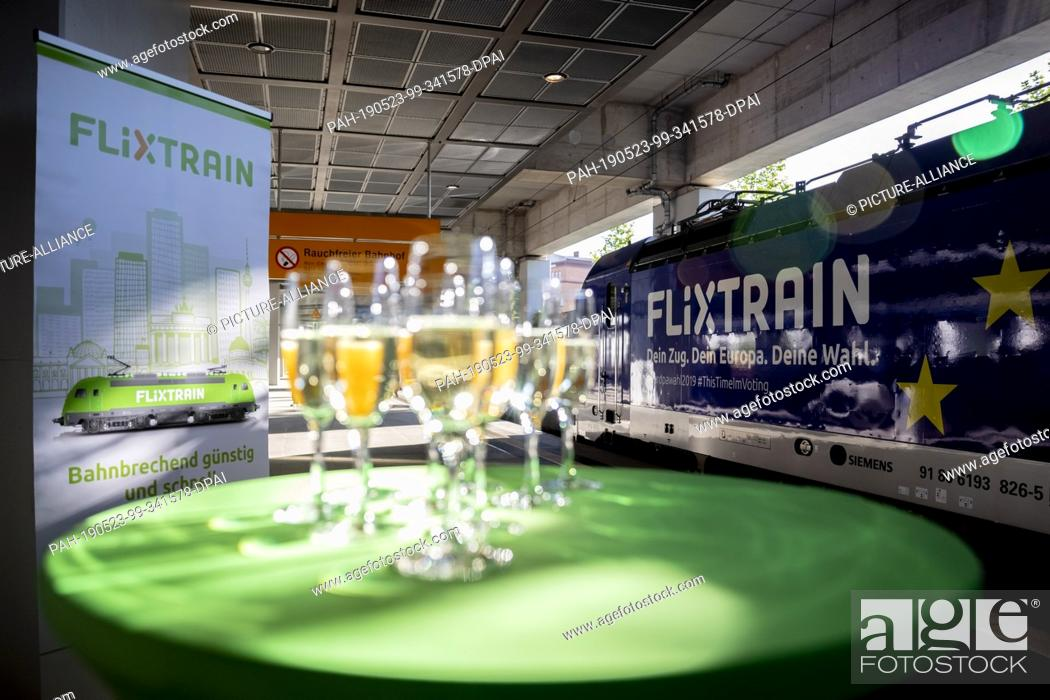 Stock Photo: 23 May 2019, North Rhine-Westphalia, Cologne: Champagne glasses are standing on a table in front of the locomotive before the first trip of the FlixTrain.