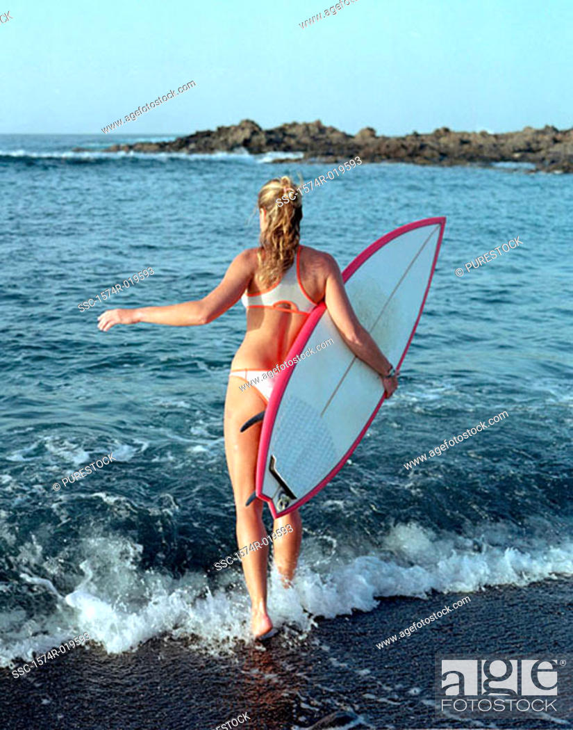 Stock Photo: Rear view of a young woman carrying a surfboard on the beach.