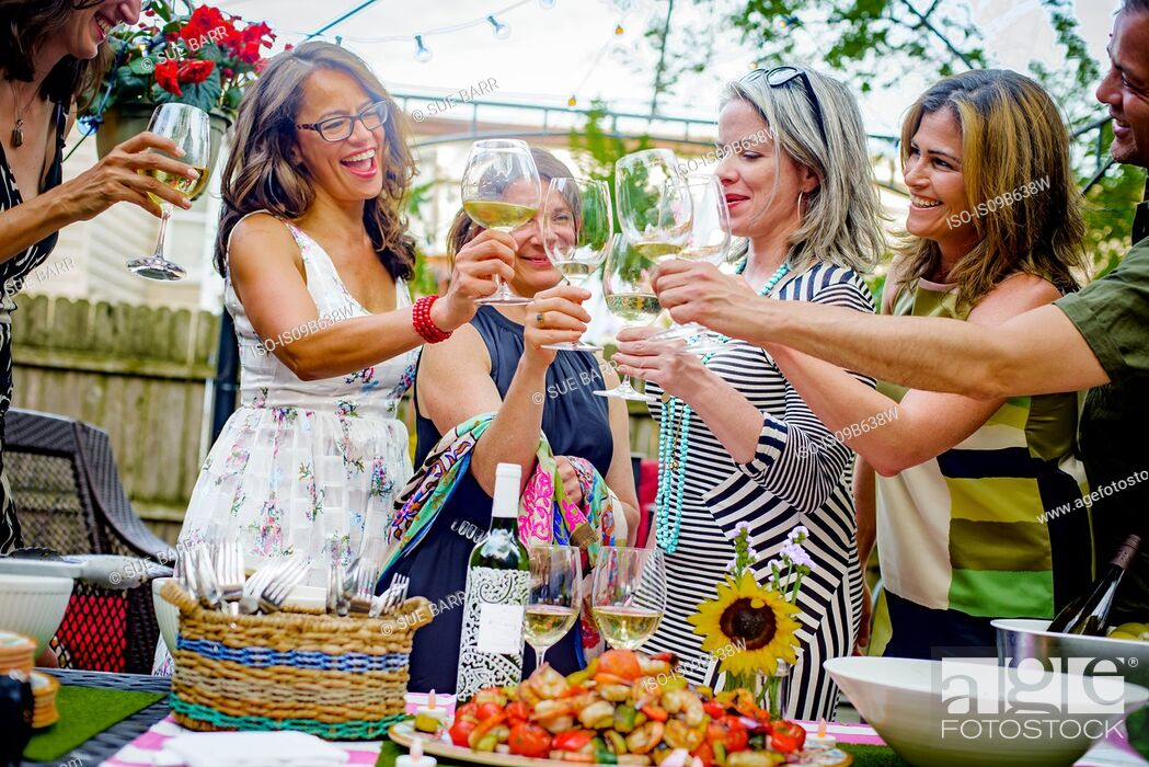 Stock Photo: Group of people at garden party, holding wine glasses, making a toast.