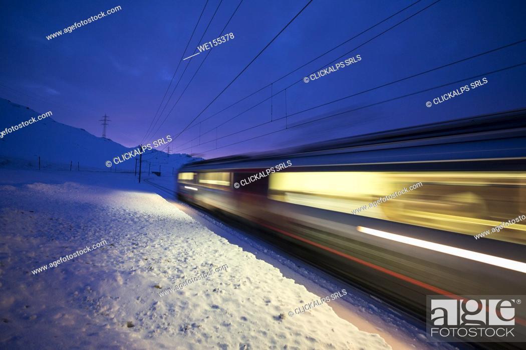 Stock Photo: Bernina Express train runs fast in the snowy landscape at dusk Bernina Pass Canton of Graubünden Engadine Switzerland Europe.