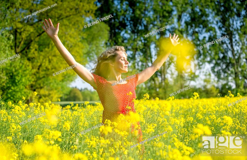 Stock Photo: Woman wearing red dress with arms raised standing amidst oilseed rapes.
