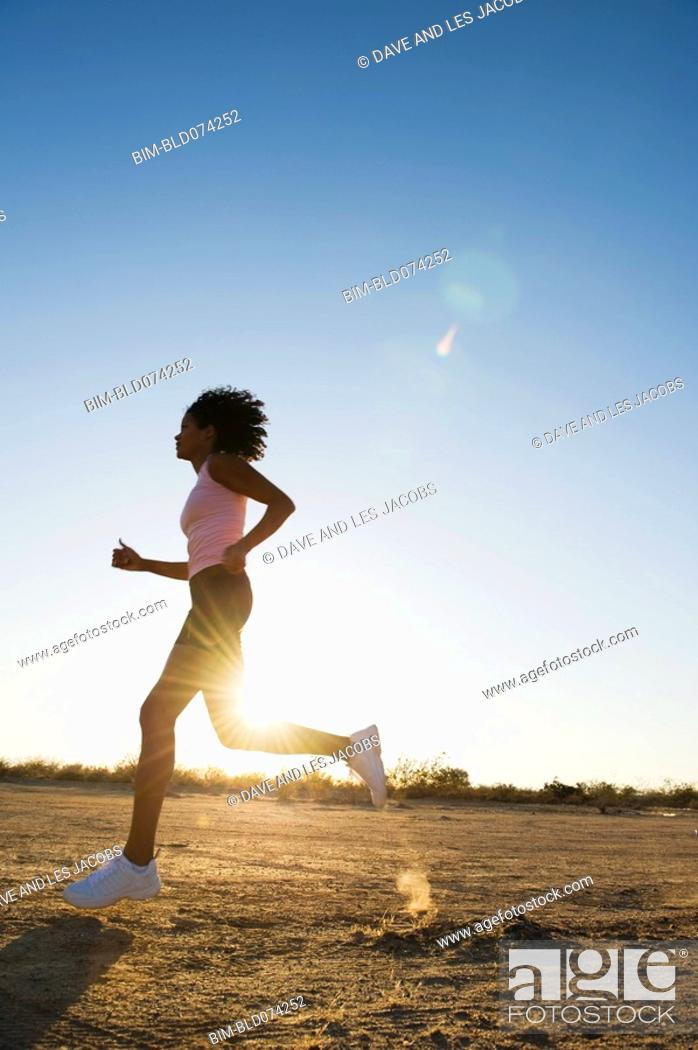 Stock Photo: African woman running on remote road.
