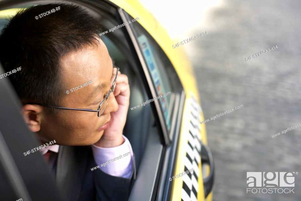 Stock Photo: Man looking out of a taxi.