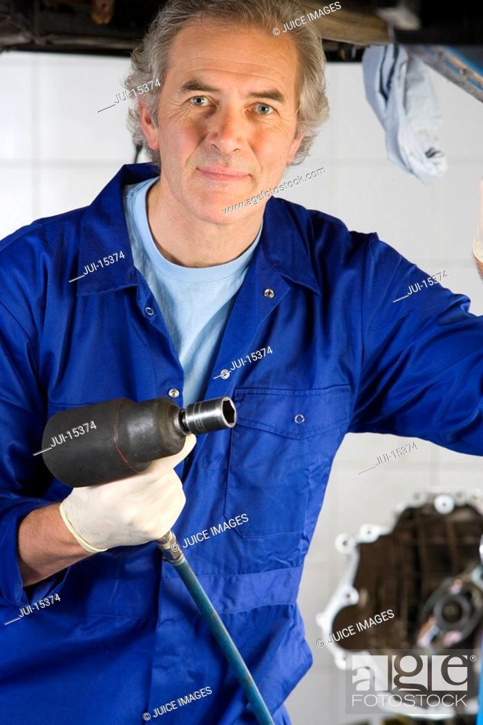 Stock Photo: Mechanic with power tool, portrait.