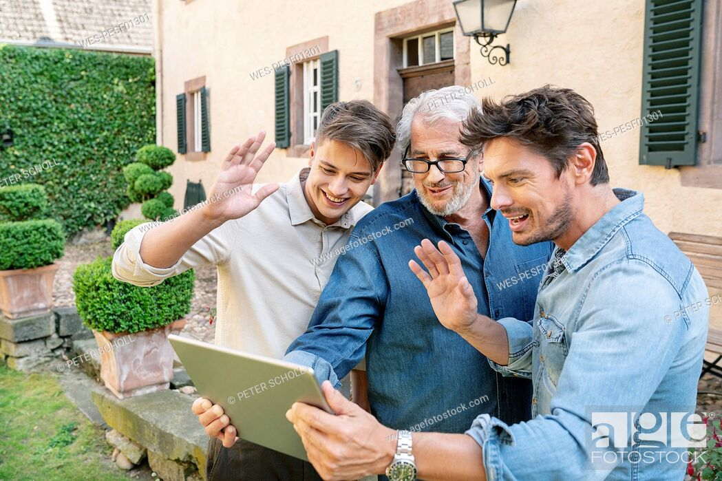 Stock Photo: Three men of different age having a video chat via tablet in garden.