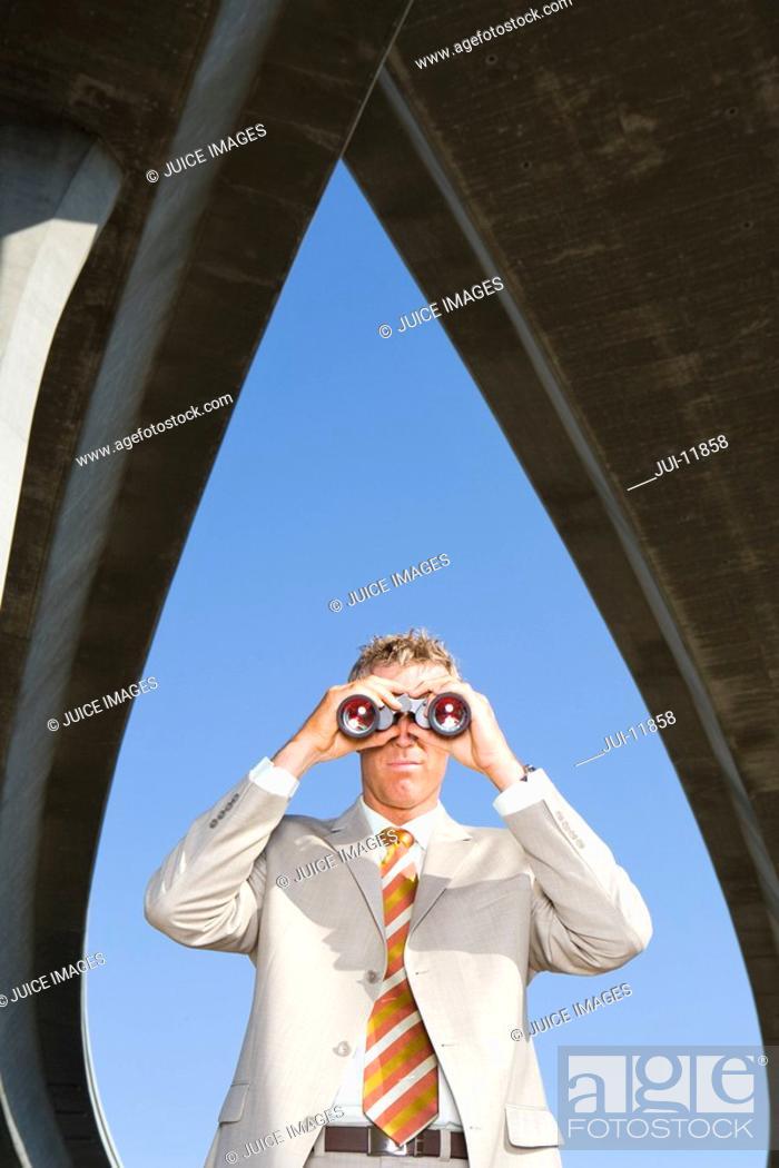 Stock Photo: Businessman using binoculars beneath overpasses, low angle view.