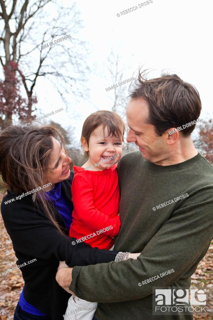 Stock Photo: Caucasian parents holding daughter outdoors.