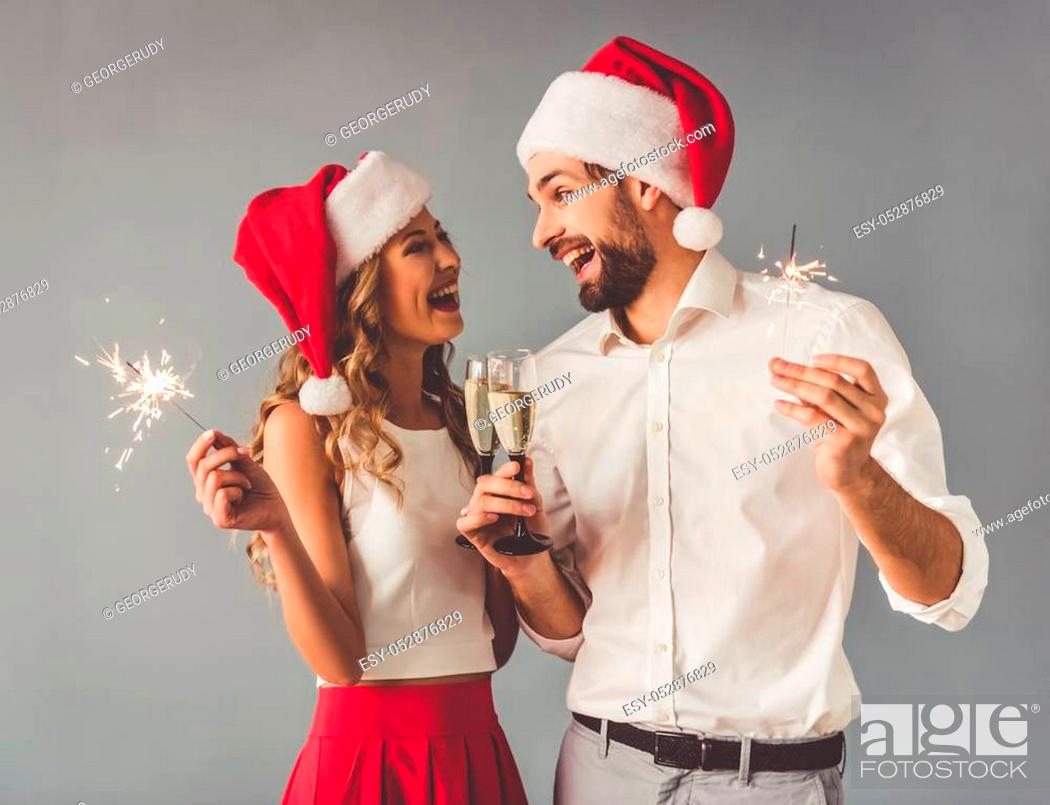 Stock Photo: Beautiful young couple in Santa hats is holding glasses of champagne and sparklers and smiling, on gray background.