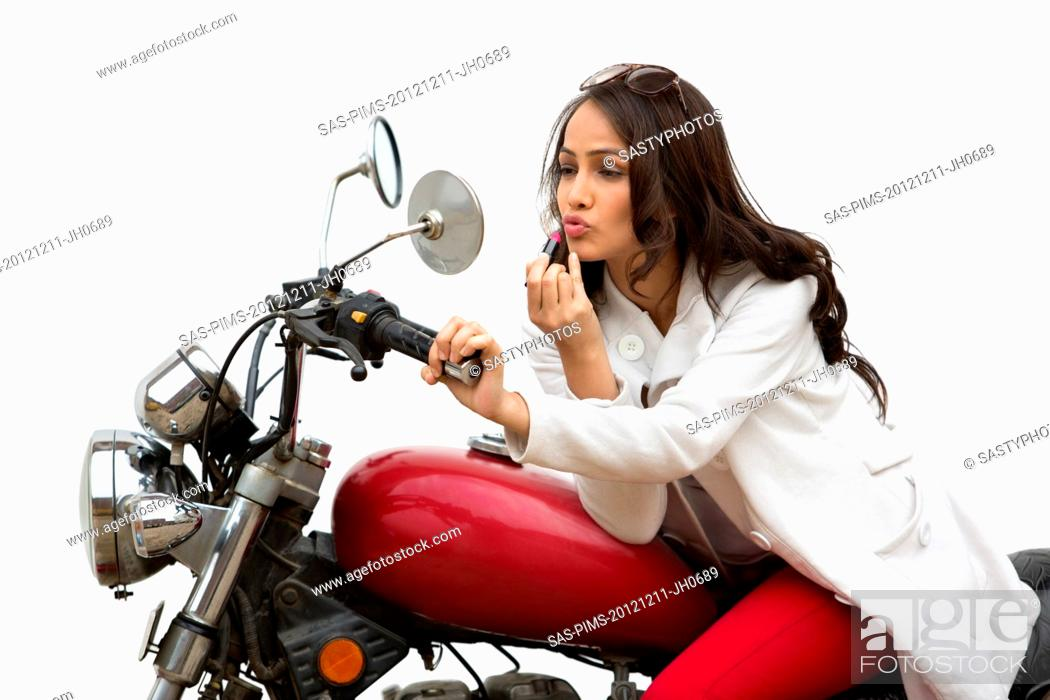 Stock Photo: Woman applying lipstick on her lips while sitting on a motorcycle.