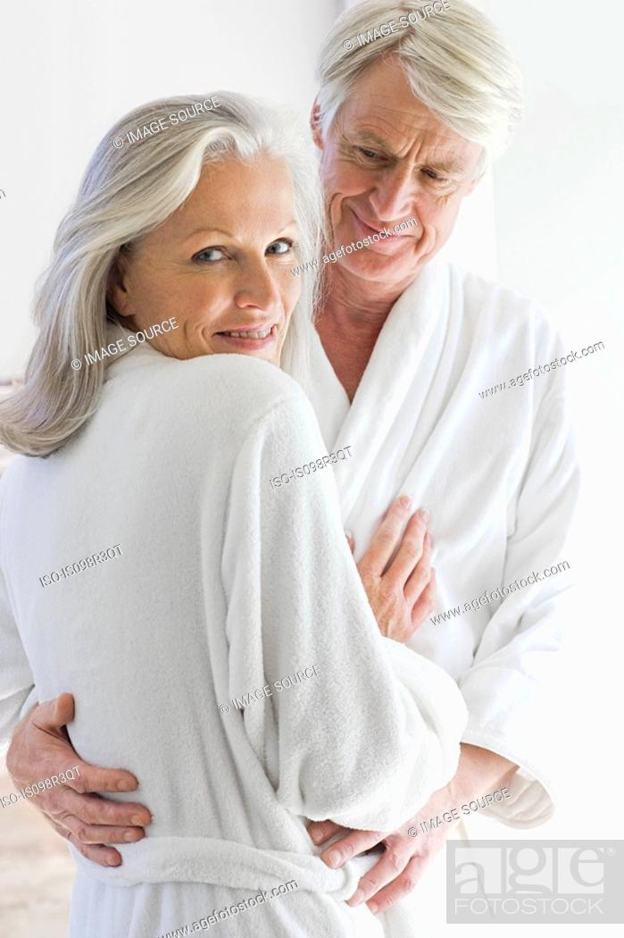 Stock Photo: Middle aged couple in bathrobes hugging.