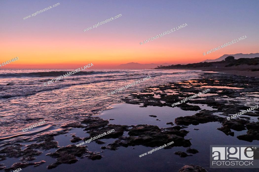 Stock Photo: Beach rocks in low tide at the sunset in Marbella Cabopino beach, orange sky and blue water.