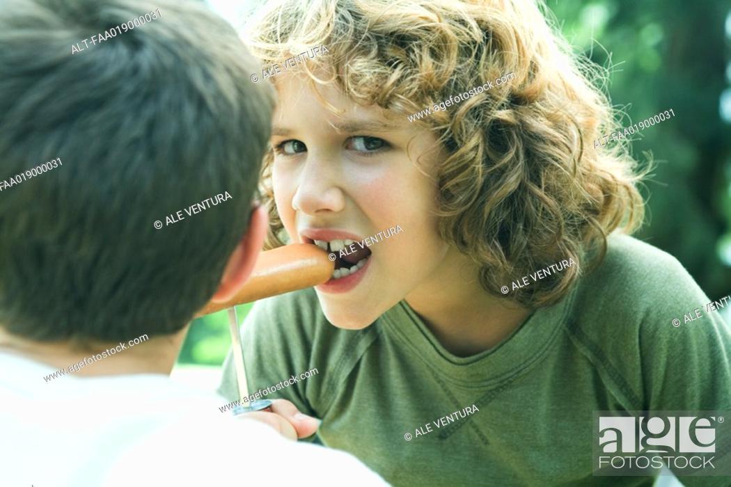 Stock Photo: Boy eating hotdog from stake.