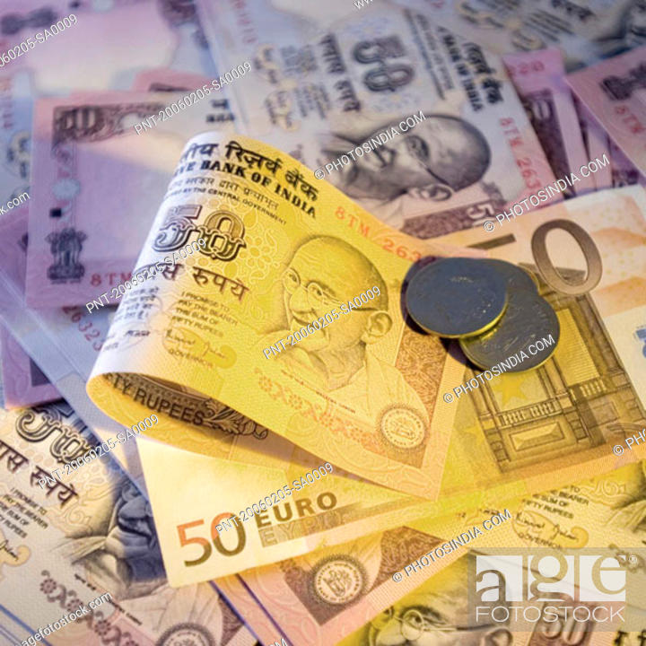 Stock Photo: High angle view of Indian banknotes and coins with a fifty Euro banknote.