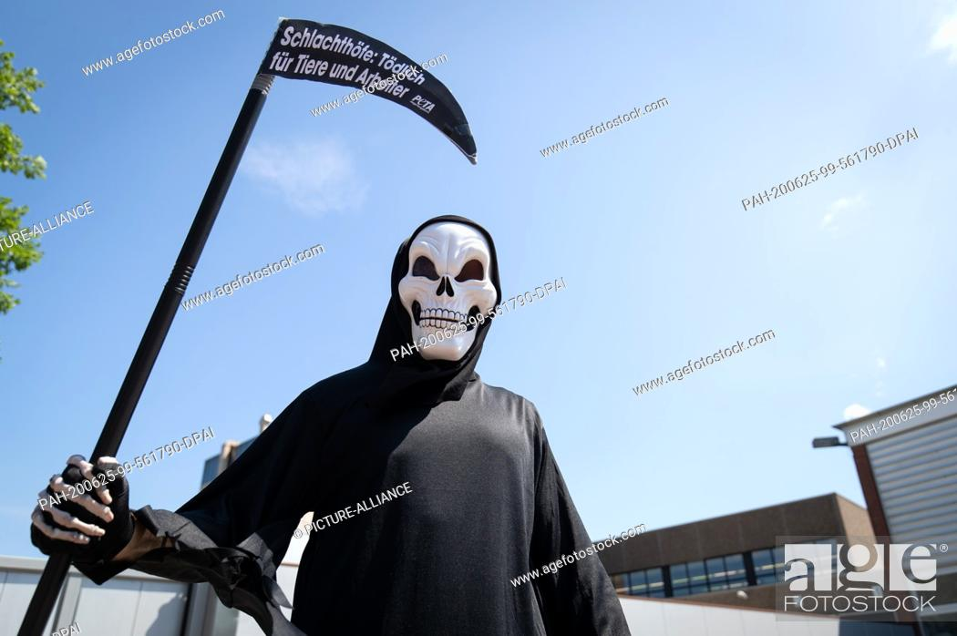 Stock Photo: 25 June 2020, Lower Saxony, Dissen: An activist of the animal protection organization Peta disguised as death stands in front of a delivery entrance of the meat.