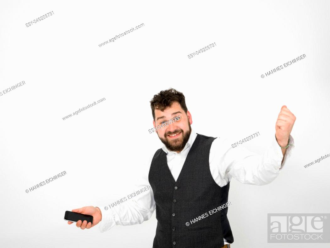 Stock Photo: young man with black beard is posing and looking at his smartphone in front of white background.