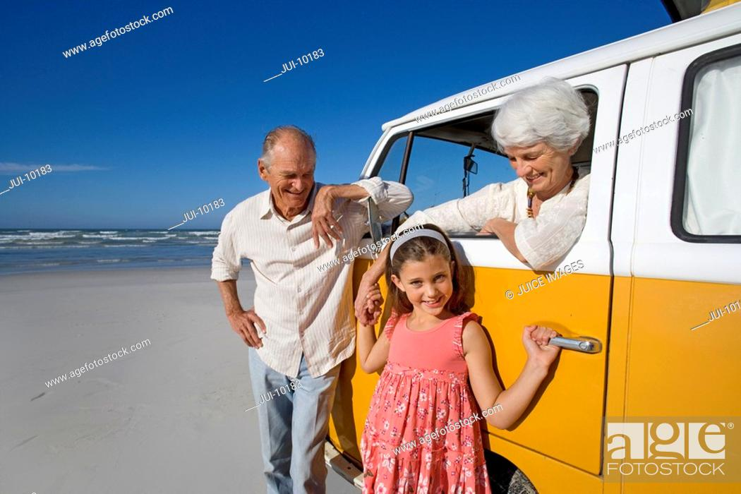 Stock Photo: Senior couple on beach, woman in camper van holding hand of granddaughter 7-9, smiling, portrait.