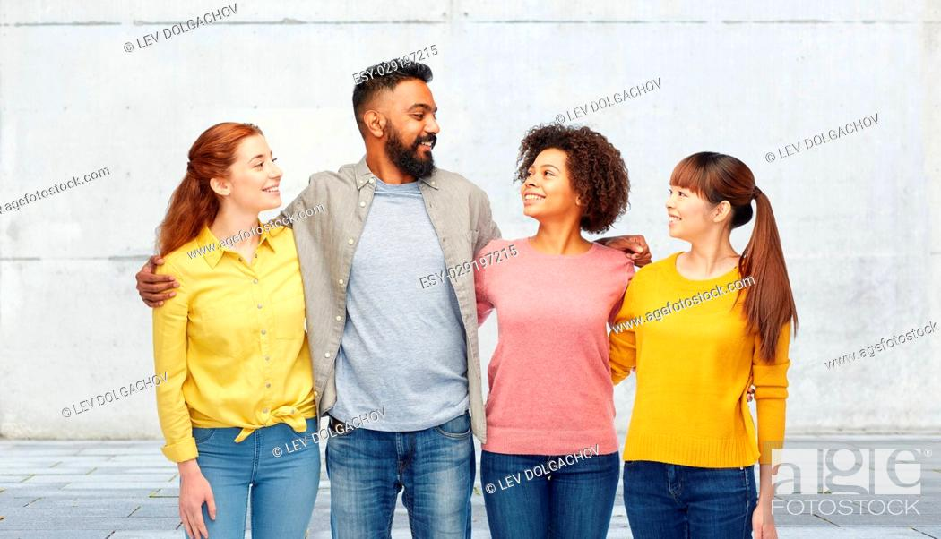 Stock Photo: diversity, race, ethnicity, friendship and people concept - international group of happy smiling men and women over stone wall background.