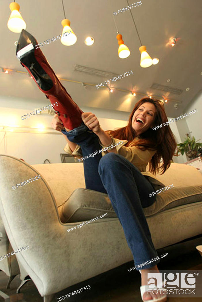 Stock Photo: Young woman trying on boots in a shoe store.