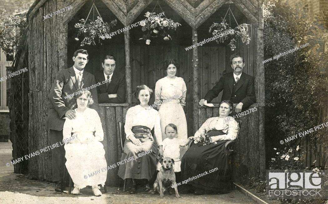 Stock Photo: Eight people with a dog in a garden.