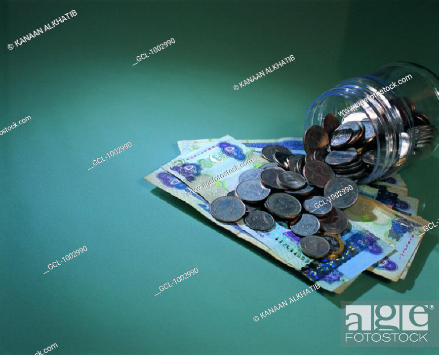 Stock Photo: United Arab Emirates banknotes and coins in a savings box.