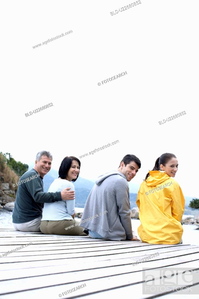 Stock Photo: Mature and young couple sitting on jetty.