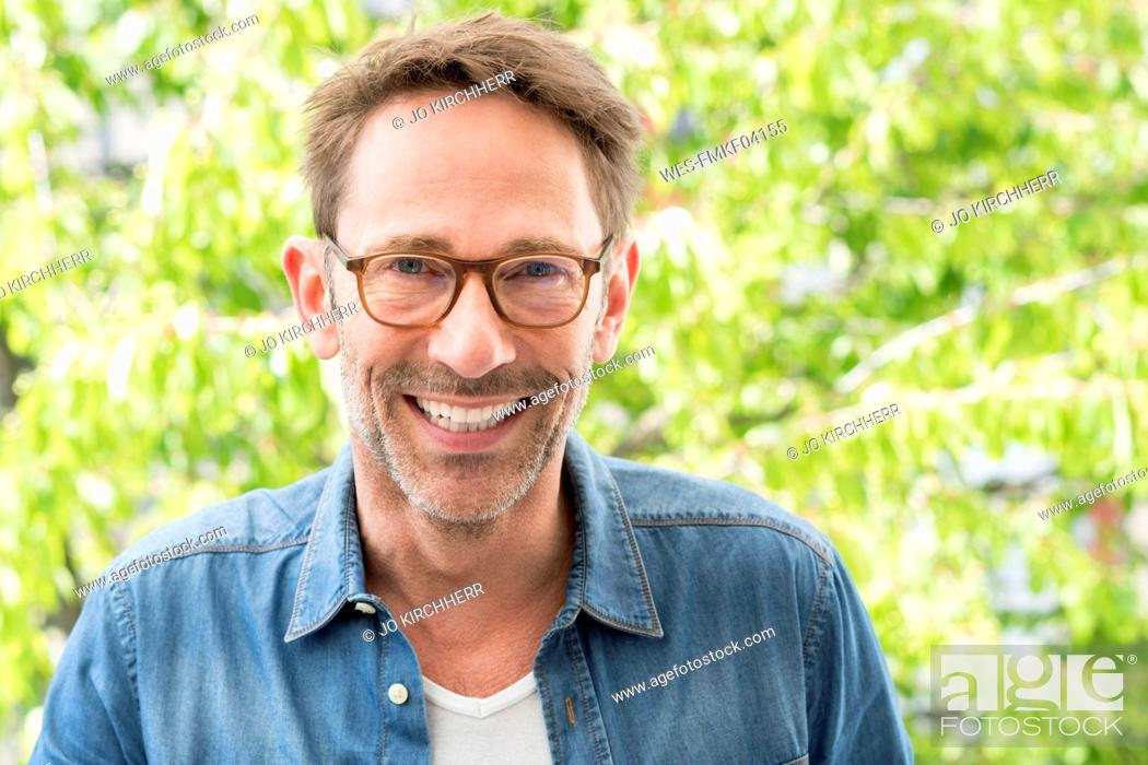 Stock Photo: Portrait of laughing mature man with stubble wearing glasses.