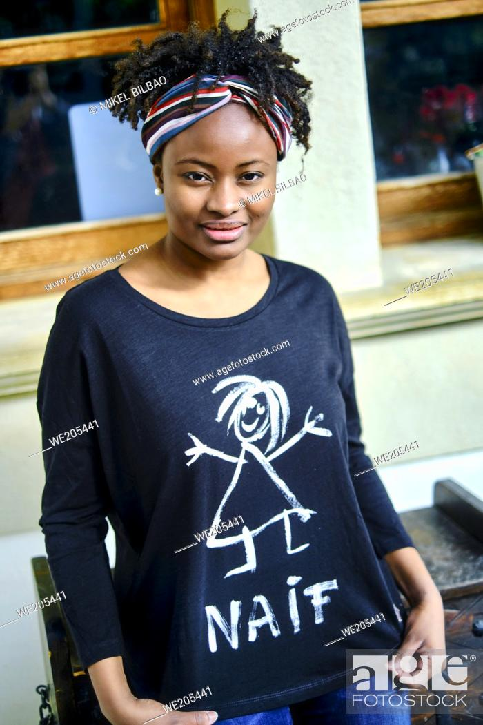 Imagen: Young african woman with an cool hair style and a t-shirt posing outdoor.