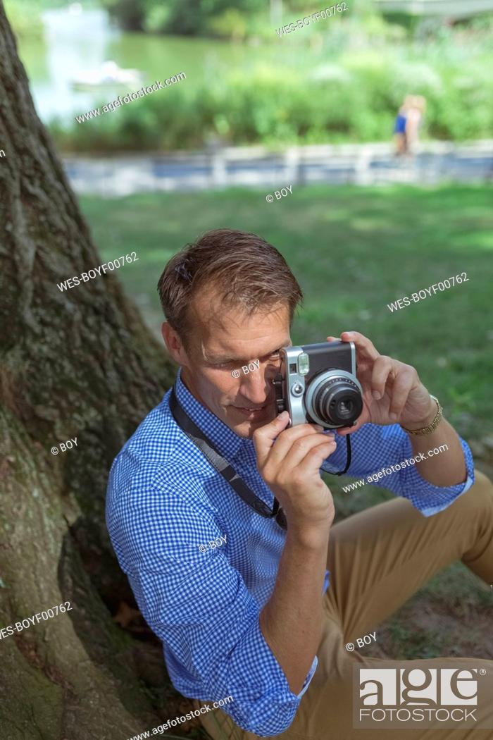 Stock Photo: Man taking pictures with camera in a park.