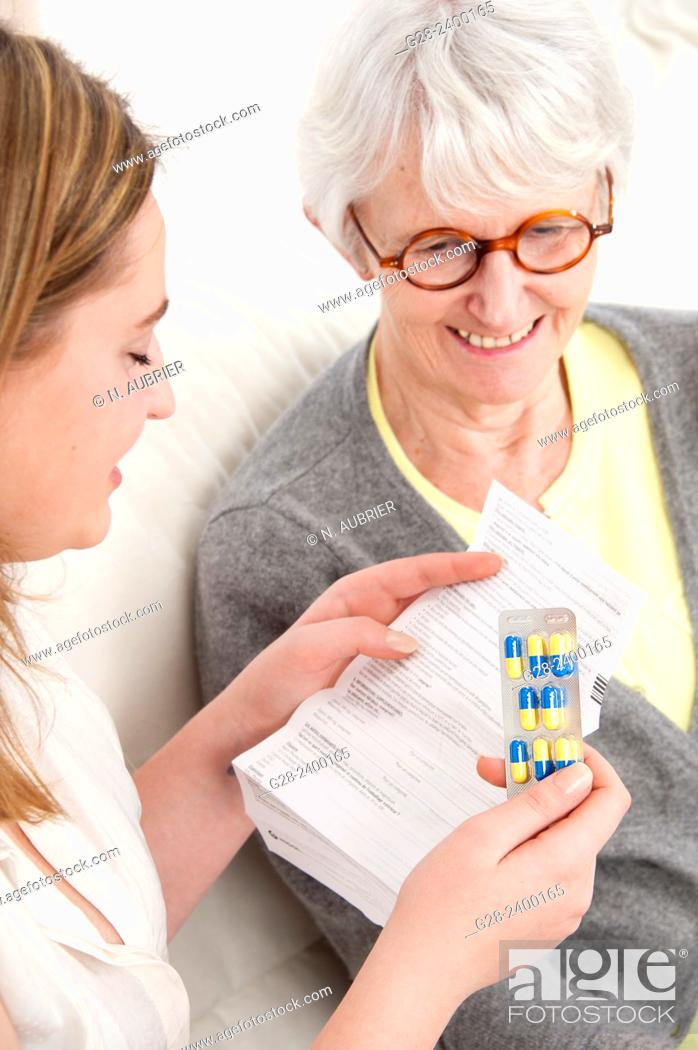 Stock Photo: Young nurse or help or granddaughter reading prescription paper, and holding tablets, for patient or grandmother who is laughing in the background.