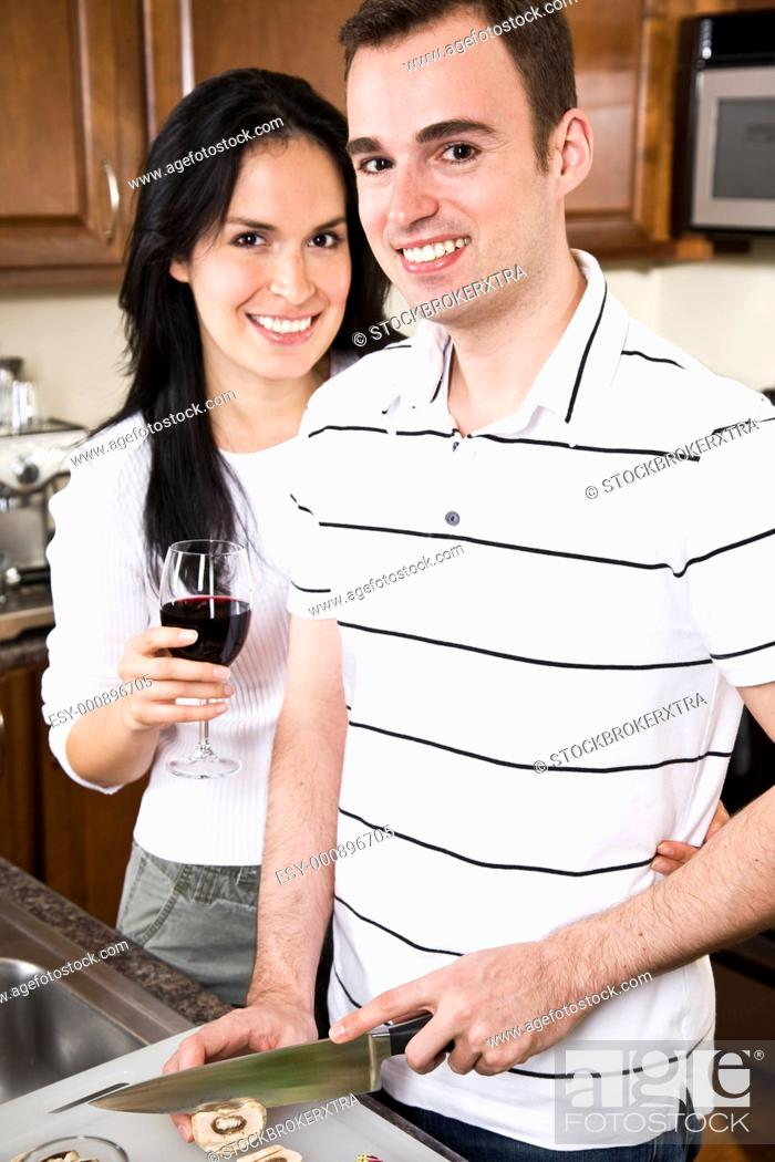 Stock Photo: A beautiful interracial couple preparing food in the kitchen.