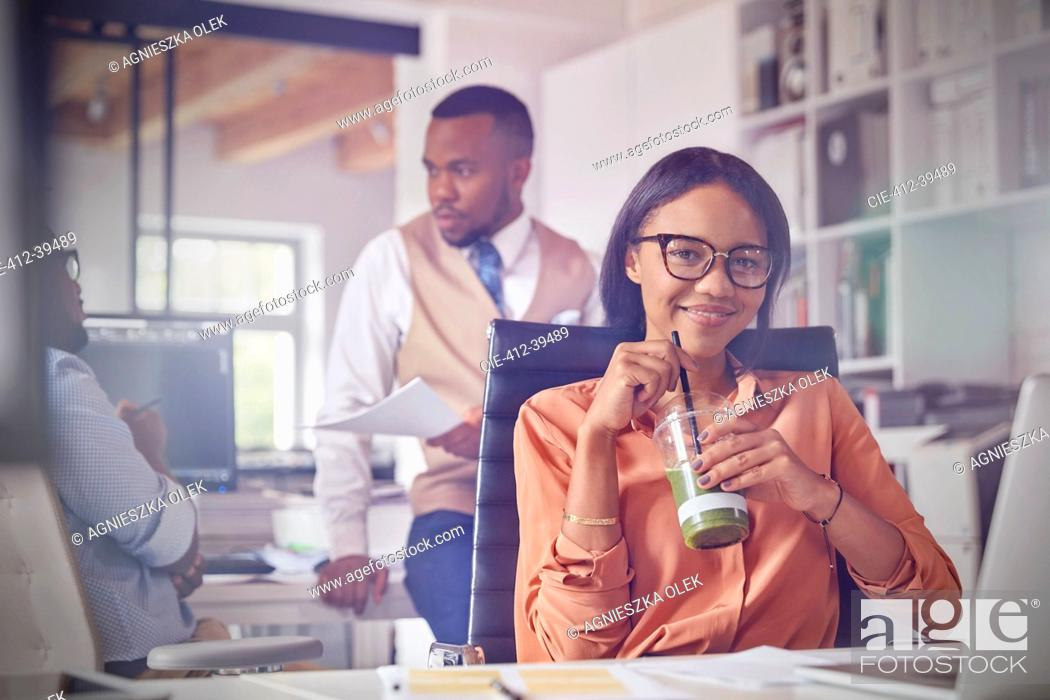 Stock Photo: Portrait smiling confident businesswoman drinking green smoothie in office.