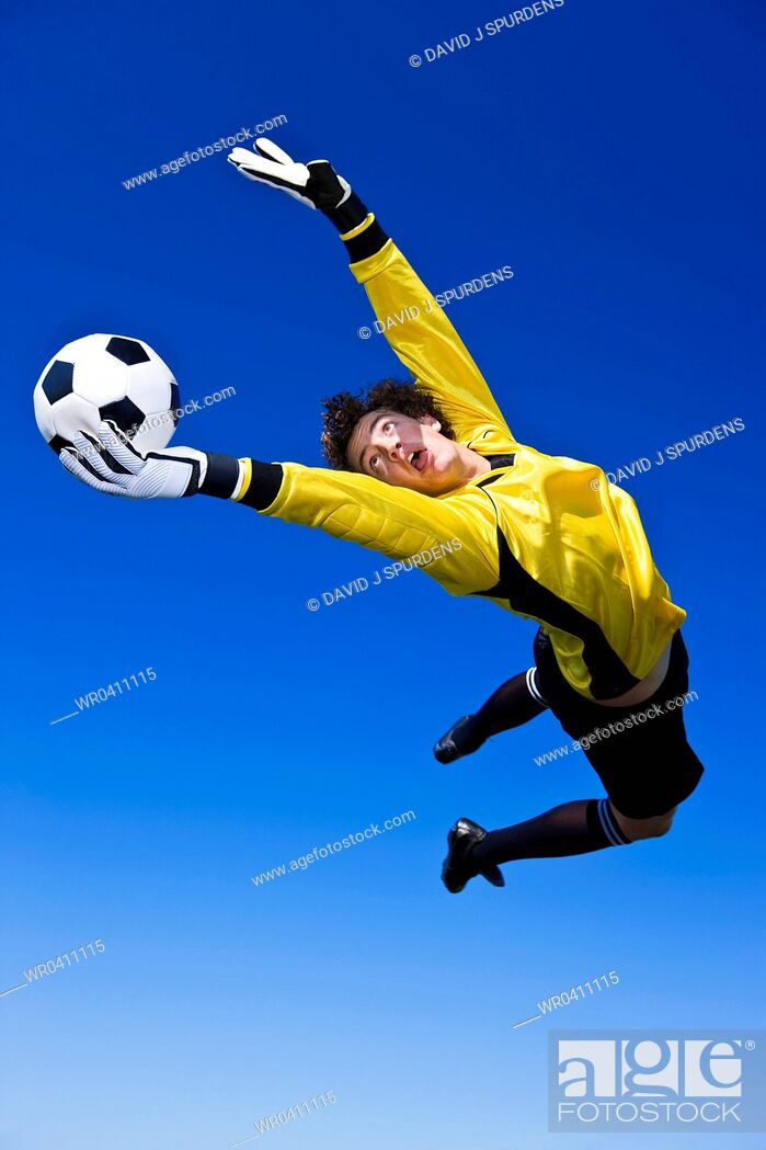 Stock Photo: A goalkeeper gets a hand to the ball to make the save.