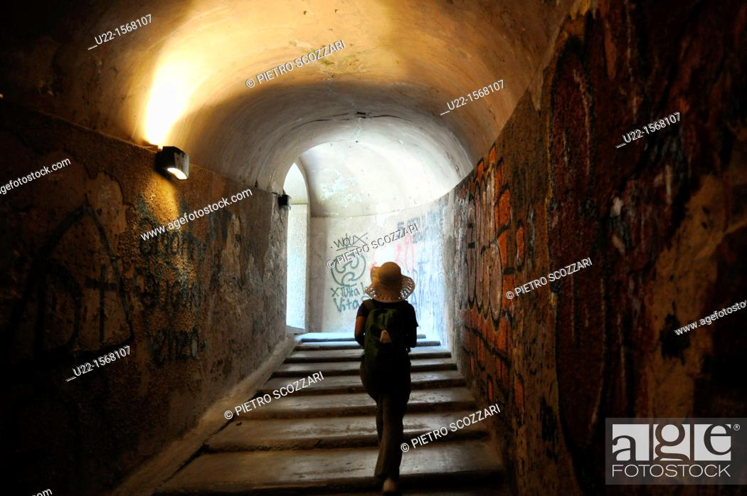 Stock Photo: Lucca (Italy): a tourist walking through a tunnel of the ancient walls that surround the city's center.