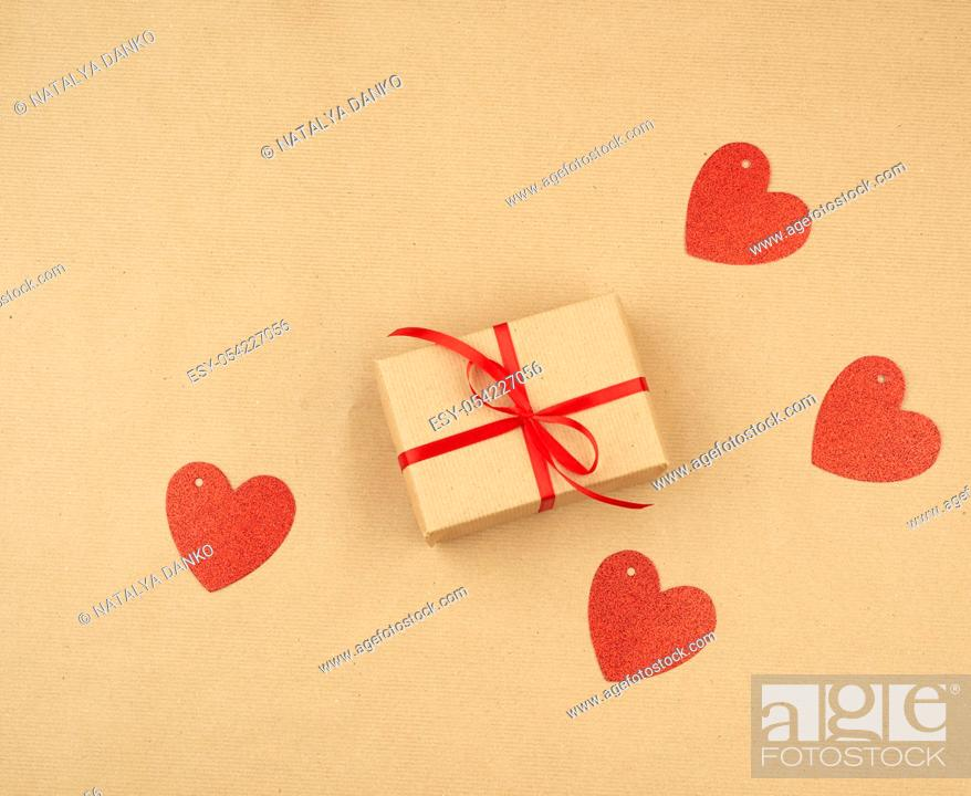 Stock Photo: gift wrapped in brown kraft paper and tied with a thin silk ribbon on a background of paper, top view. Congratulations on Valentine's Day February 14.
