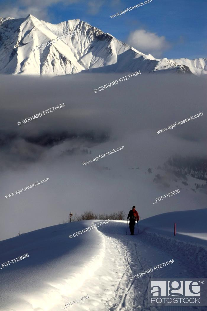 Stock Photo: Hiker walking snowy footpath with view of mountain range in background.
