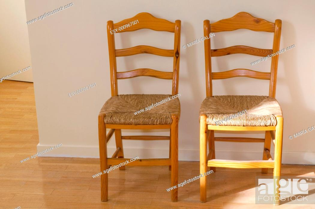 Stock Photo: Two wooden chairs, with wickerwork seats.