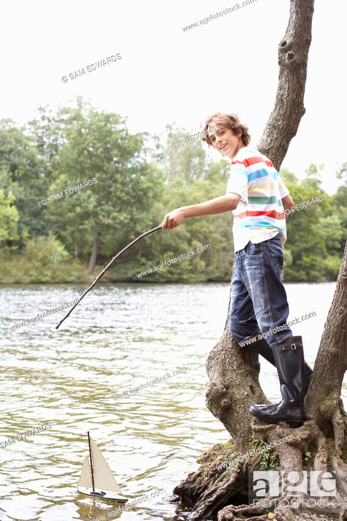 Stock Photo: Boy playing with toy sailboat in lake.