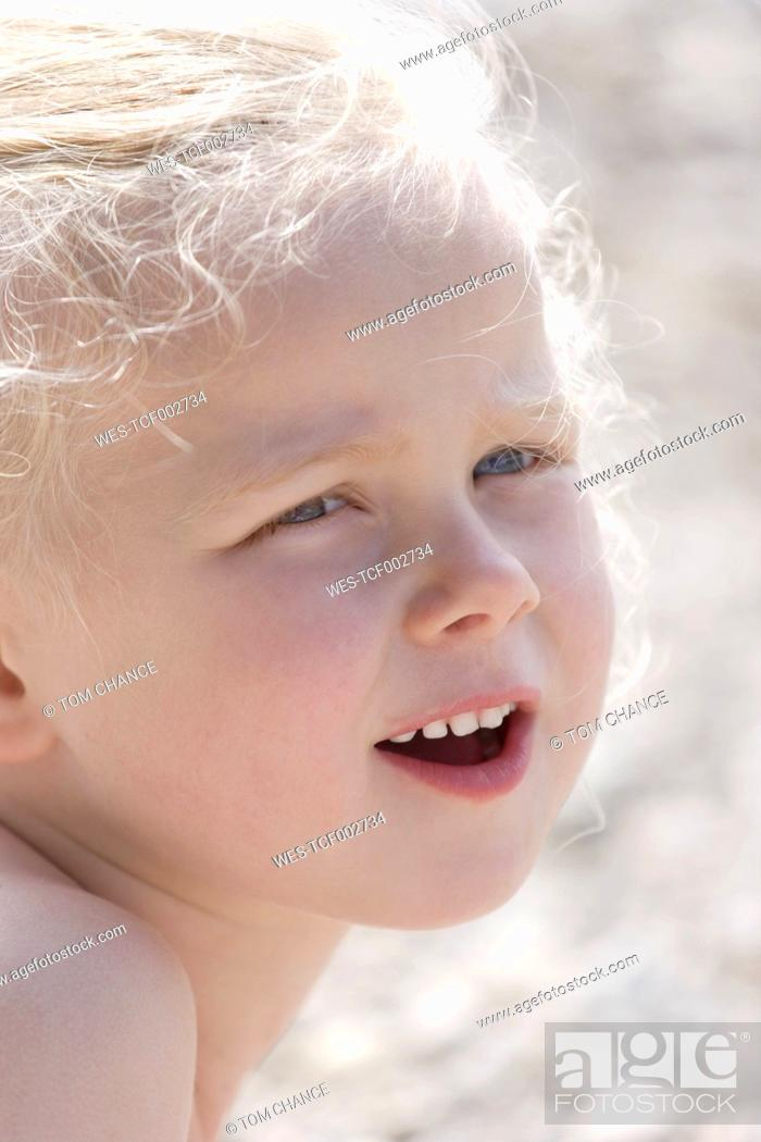 Stock Photo: Germany, Bavaria, Girl looking away, smiling, close up.