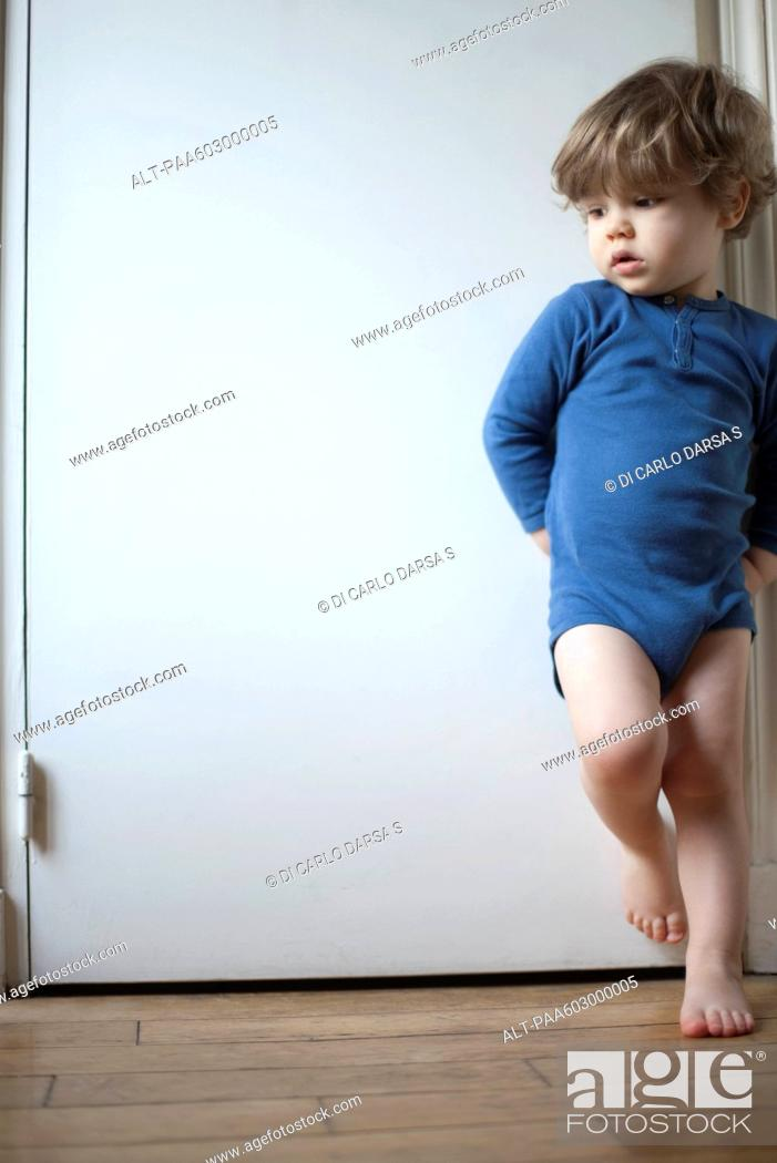 Stock Photo: Toddler boy standing on one leg against door, looking away in thought, portrait.