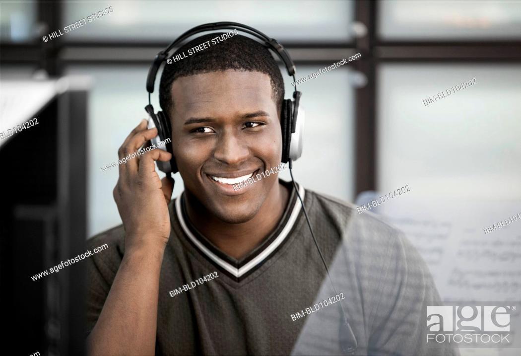 Stock Photo: Black man listening to music on headphones.