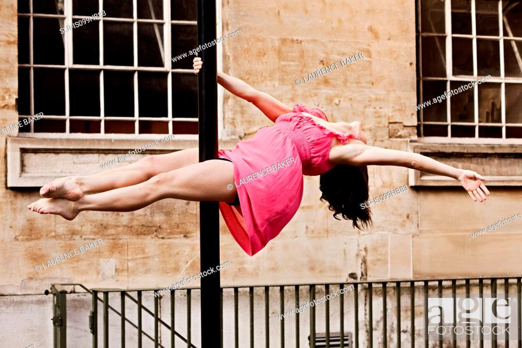 Stock Photo: Woman in pink dress performing dance on street lamp in city.