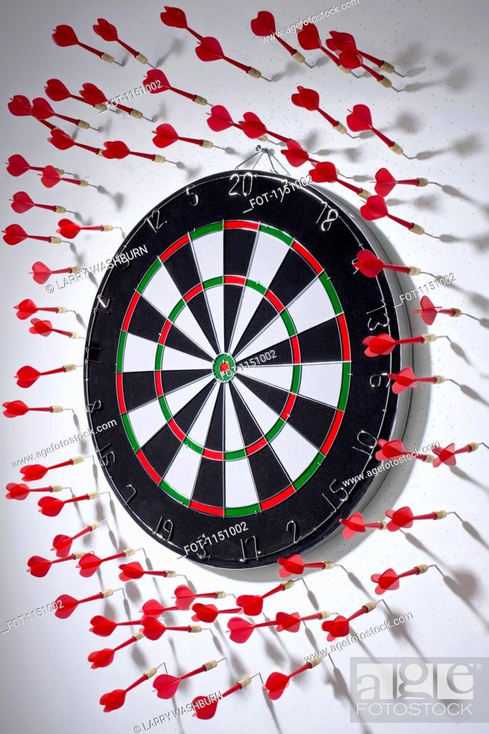 Stock Photo: Multiple darts stuck in a wall all around a dartboard.