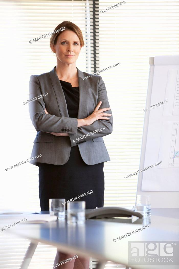 Stock Photo: Portrait of confident businesswoman with arms crossed.