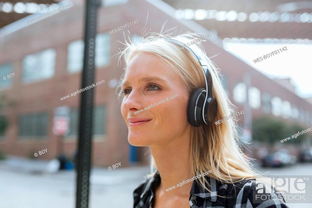 Stock Photo: USA, New York City, Brooklyn, smiling young woman listening to music with headphones in the city.