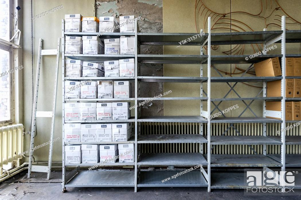 Photo de stock: Rotterdam, Netherlands. Companies and enterprise accounts and archives, stored inside large, metal racks in an abandoned and former employees cantina building.