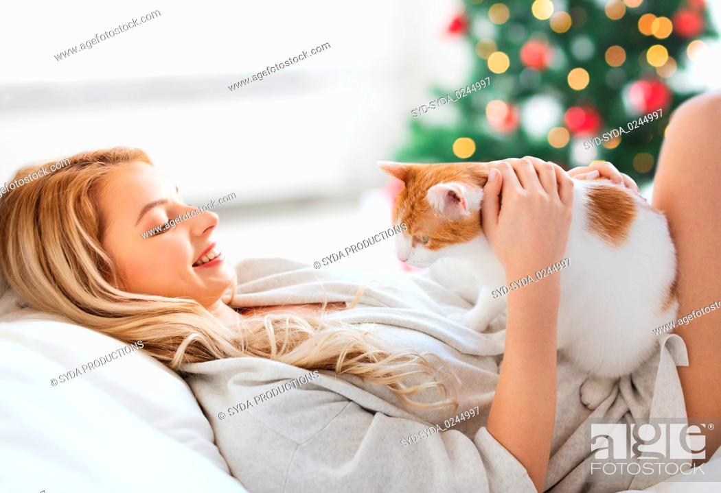 Stock Photo: happy young woman with cat in bed at christmas.