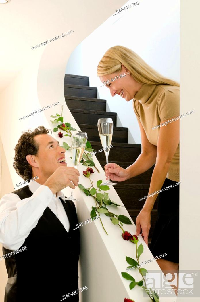 Stock Photo: Couple holding champagne glasses on staircase decorated with red roses.